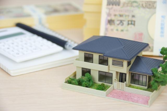 家の模型と電卓、札束